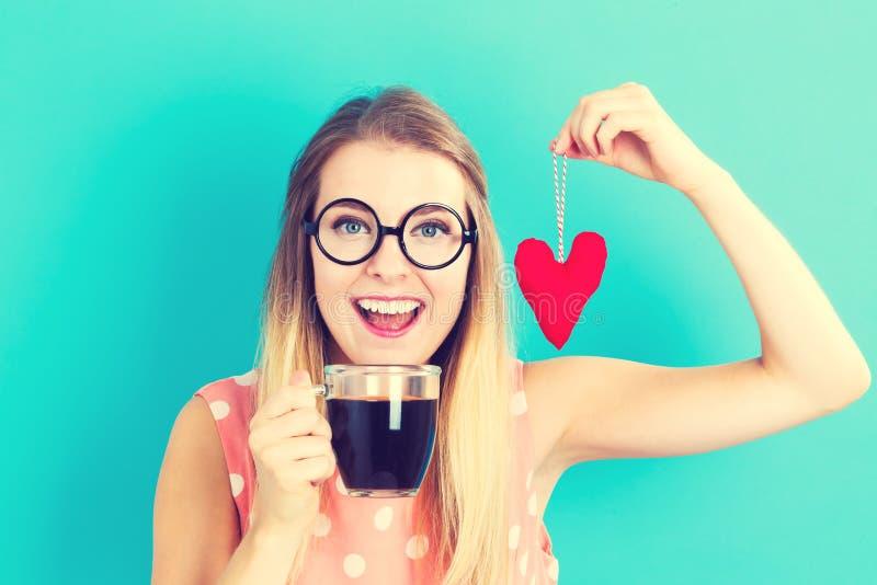 Café de consumición de la mujer con el amortiguador del corazón fotografía de archivo libre de regalías