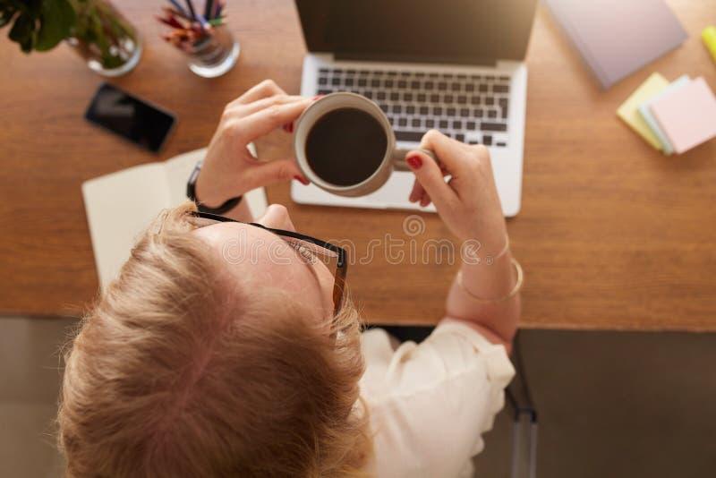 Café de consumición de la mujer en su escritorio imagen de archivo libre de regalías