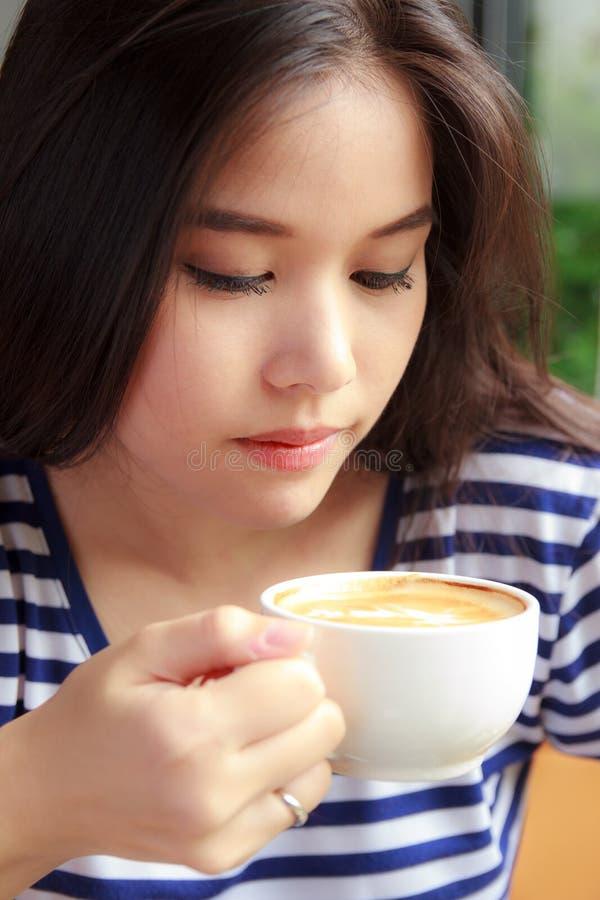 Café de consumición de la mujer en un café foto de archivo