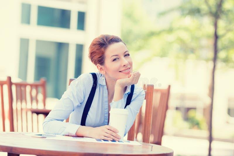 Café de consumición de la mujer feliz en sentarse del sol al aire libre fotografía de archivo libre de regalías
