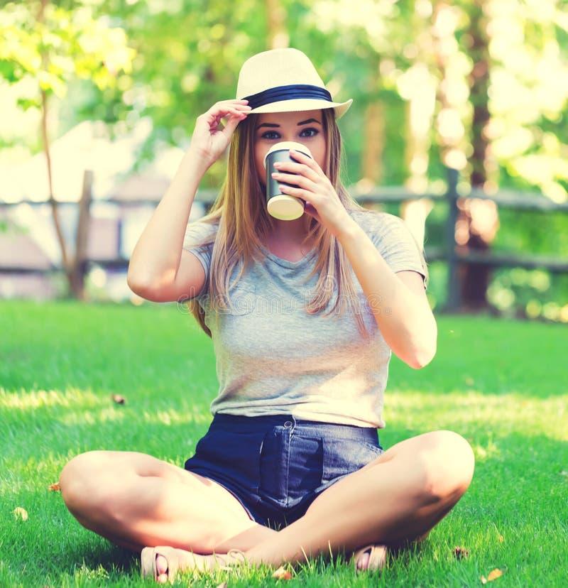 Café de consumición de la mujer joven afuera imagenes de archivo