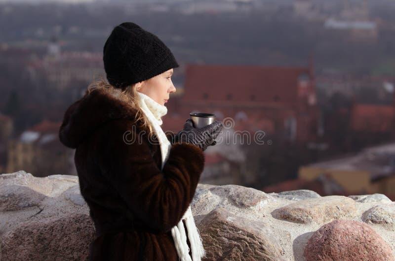 Café de consumición de la mujer joven en Vilna fotografía de archivo