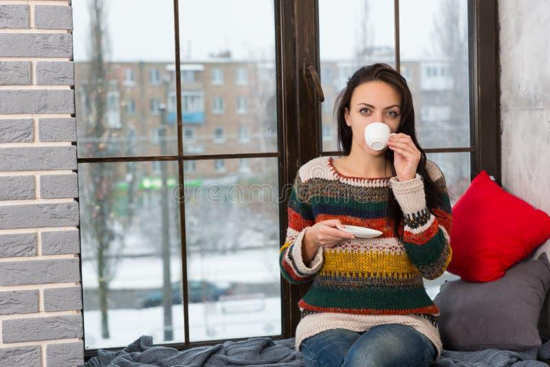Café de consumición de la mujer joven mientras que se sienta en alféizar imagen de archivo libre de regalías