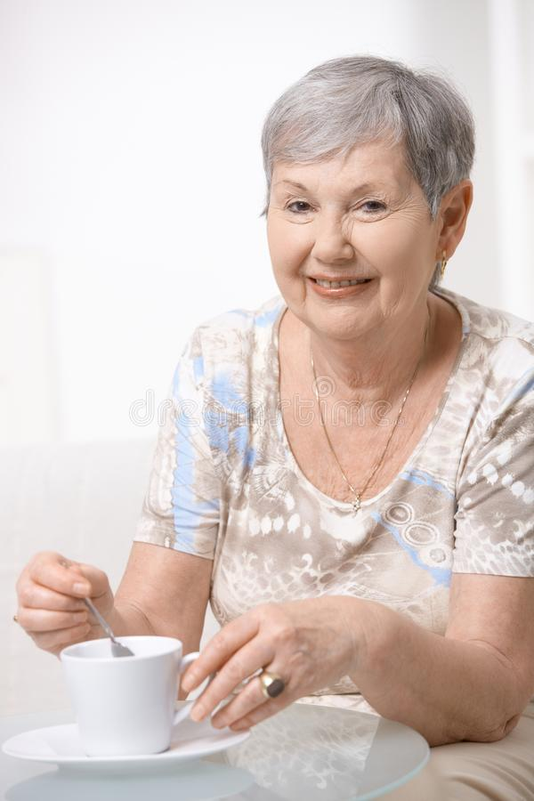Café de consumición de la mujer mayor feliz fotografía de archivo libre de regalías