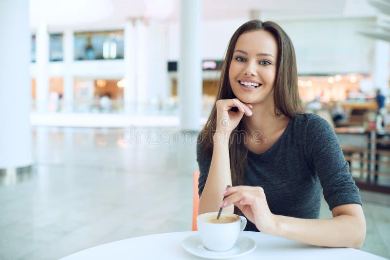 Café de consumición de la mujer por la mañana en el foco suave del restaurante imagenes de archivo