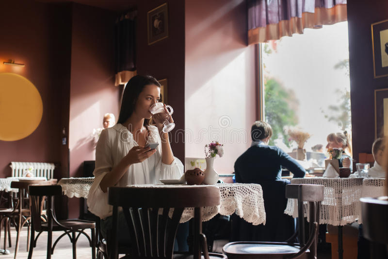 Café de consumición de la mujer por la mañana en el foco suave del restaurante foto de archivo libre de regalías