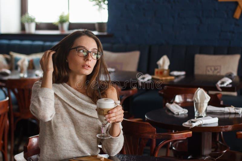 Café de consumición de la mujer por la mañana en el foco suave del restaurante en los ojos imágenes de archivo libres de regalías