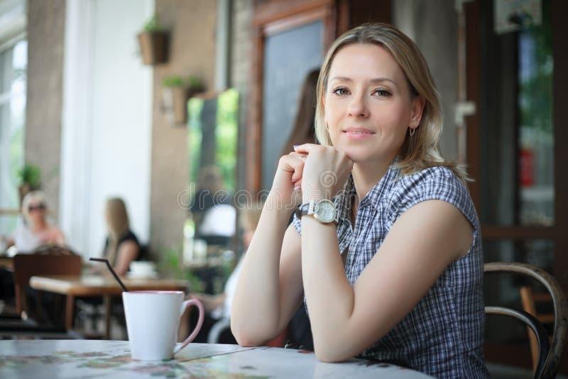 Café de consumición de la mujer por la mañana en el restaurante foto de archivo