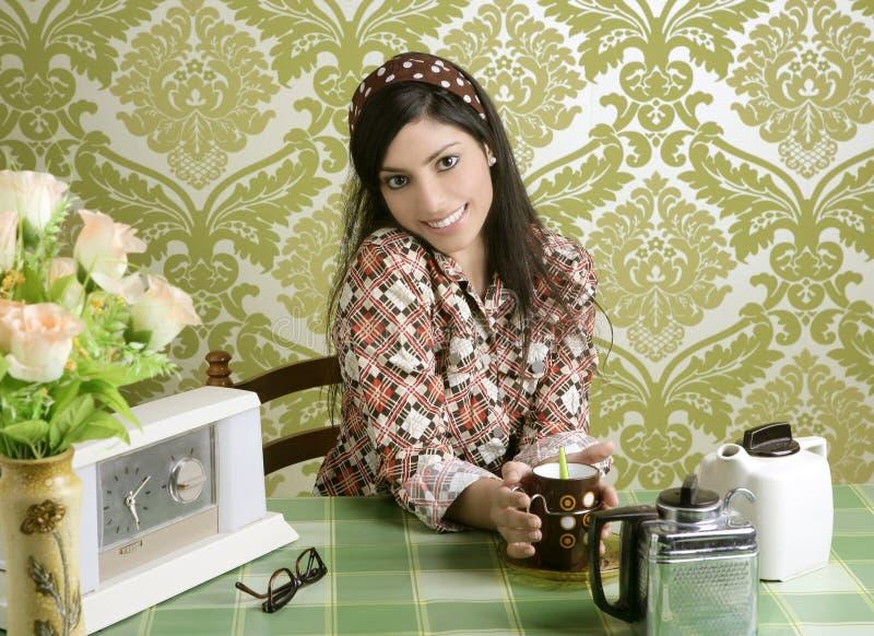 Café de consumición de la mujer retra en cocina del papel pintado imagen de archivo