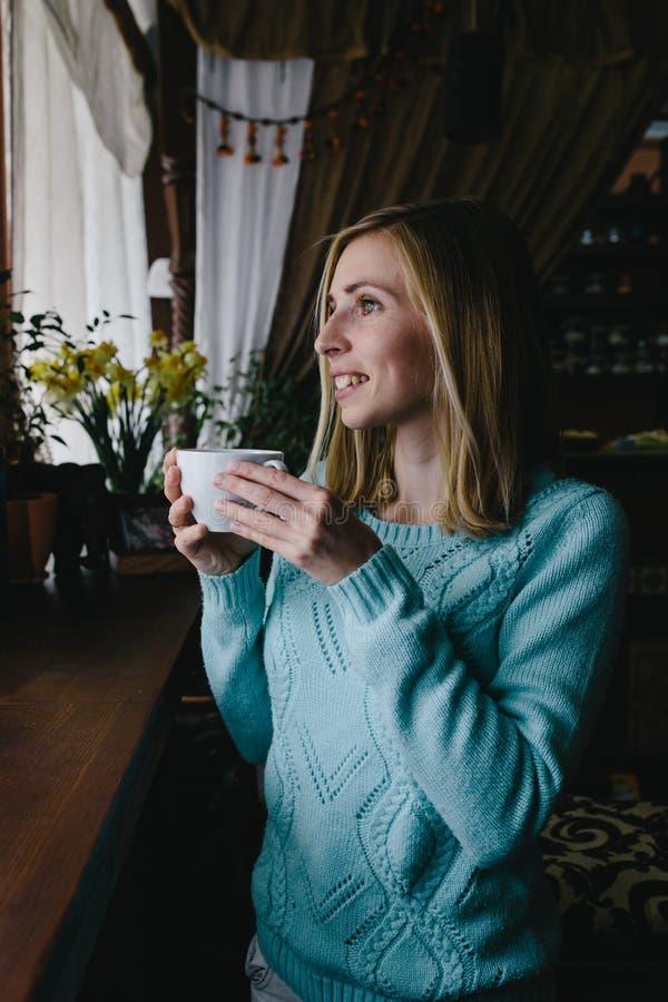 Café de consumición de la mujer vertical de la foto por la mañana en el restauran imagen de archivo