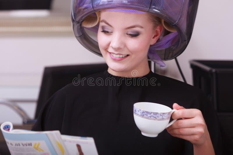 Café de consumición de la revista de la lectura de la muchacha. Hairdryer en salón de belleza del pelo fotos de archivo libres de regalías