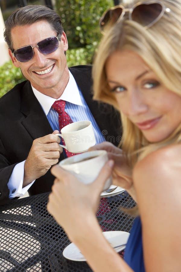 Café de consumición de los pares del hombre de negocios y de la mujer imagen de archivo