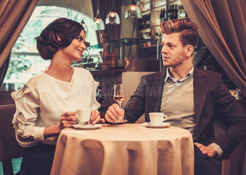 Café de consumición de los pares elegantes en restaurante fotografía de archivo libre de regalías