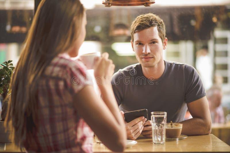 Café de consumición de los pares jovenes fotos de archivo