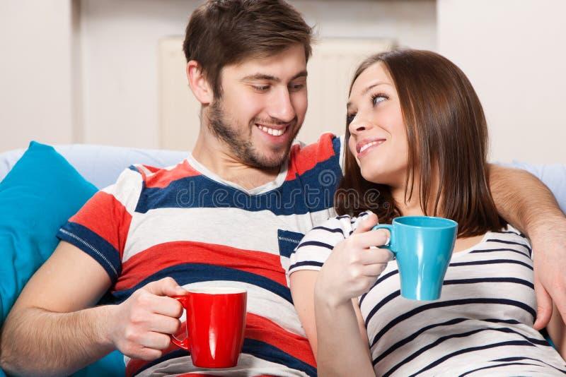 Café de consumición de los pares jovenes en casa fotografía de archivo libre de regalías