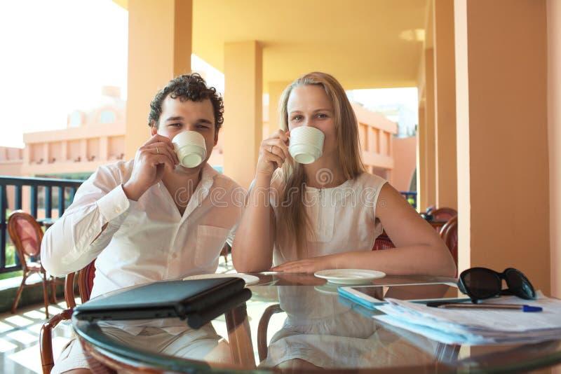 Café de consumición de los pares jovenes en un balcón foto de archivo