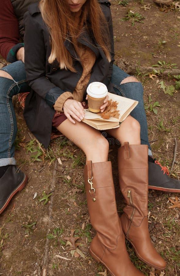 Café de consumición de los pares románticos que se relaja en el parque en otoño imagen de archivo