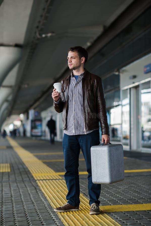 Café de consumición del hombre atractivo joven en su manera cerca del terminal de aeropuerto que mira a la cámara foto de archivo