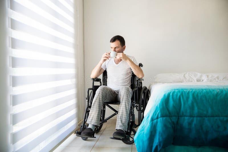 Café de consumición del hombre discapacitado en casa imagen de archivo libre de regalías