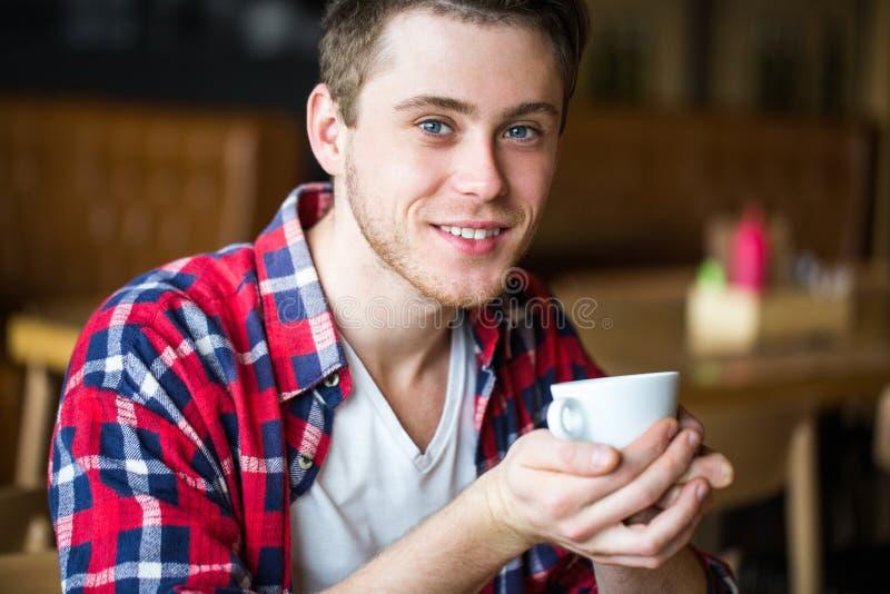 Café de consumición del hombre en un café hombre que sostiene una taza de té del café fotografía de archivo libre de regalías