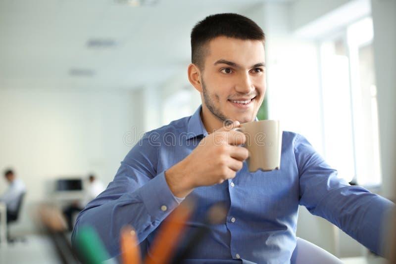 Café de consumición del hombre joven mientras que trabaja foto de archivo