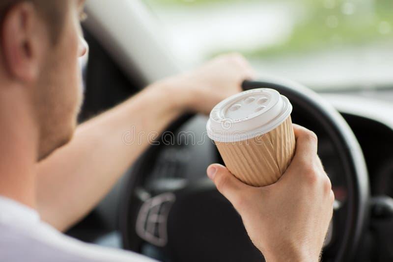 Café de consumición del hombre mientras que conduce el coche imagenes de archivo