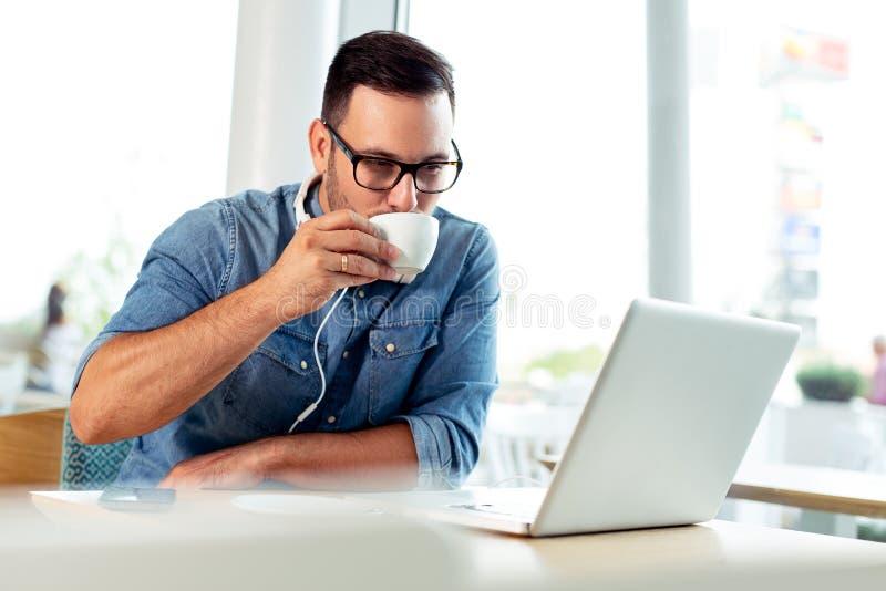 Café de consumición del hombre de negocios atractivo joven y mirada de su ordenador foto de archivo libre de regalías