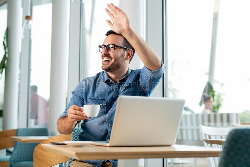 Café de consumición del hombre de negocios atractivo joven y mirada de su ordenador - Imagen fotos de archivo libres de regalías
