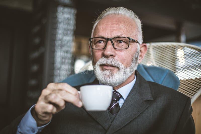 Café de consumición del hombre de negocios del Senor Relaje el tiempo imagenes de archivo
