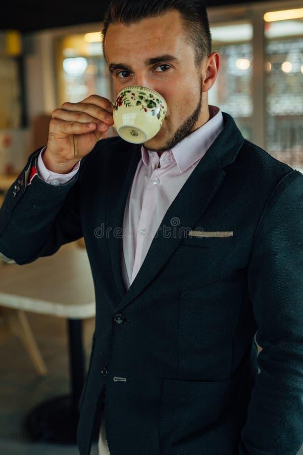 Café de consumición enfocado jóvenes del hombre de negocios en café Foto interior fotografía de archivo
