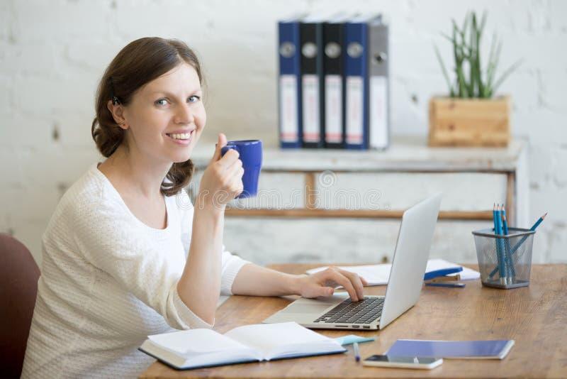 Café de consumición joven de la mujer de negocios en el lugar de trabajo imagenes de archivo
