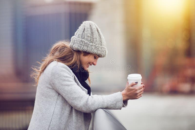 Café de consumición joven feliz hermoso de la mujer adulta cerca de la ropa y de la sonrisa del invierno del horizonte de New Yor fotos de archivo