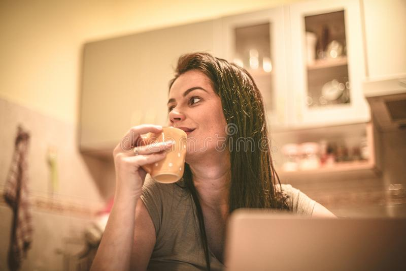 Café de consumición de la cocina de la mujer joven en casa fotografía de archivo