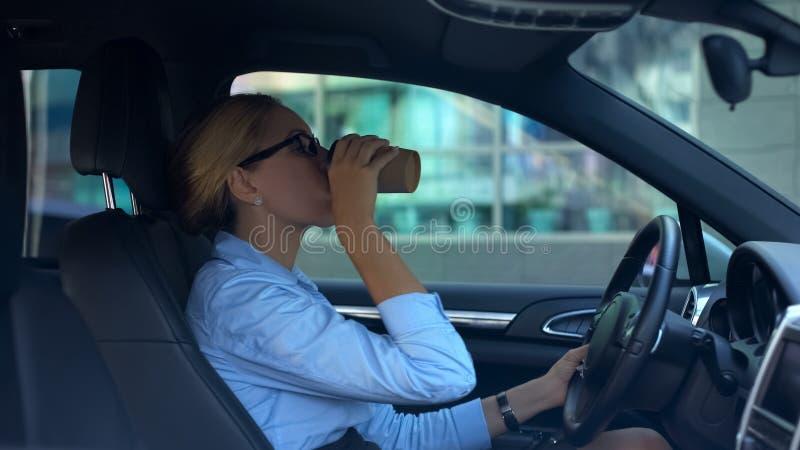 Café de consumición de la empresaria mientras que conduce el coche, falta de sueño, forma de vida ocupada imagen de archivo libre de regalías
