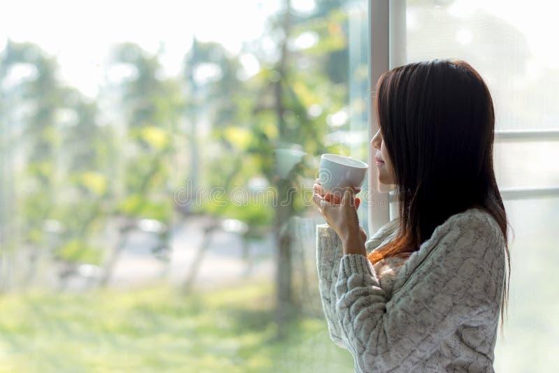 Café de consumición de la mañana fresca asiática de la mujer y mirada fuera de la ventana el día soleado imágenes de archivo libres de regalías