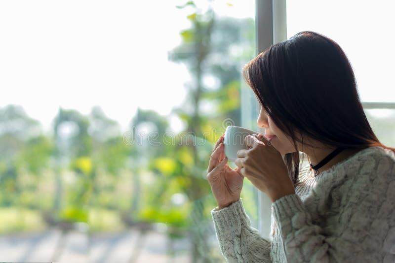 Café de consumición de la mañana fresca asiática de la mujer y mirada fuera de la ventana el día soleado imagenes de archivo