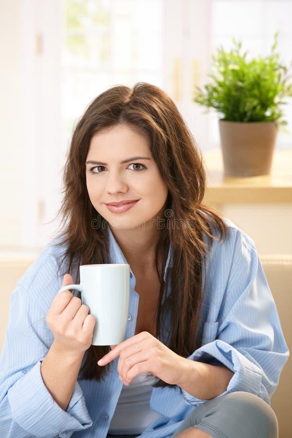 Café de consumición de la mañana de la mujer joven fotografía de archivo libre de regalías