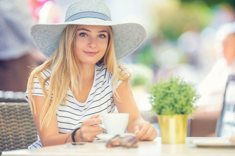 Café de consumición de la muchacha hermosa en una terraza del café Mujer joven del retrato del verano fotos de archivo