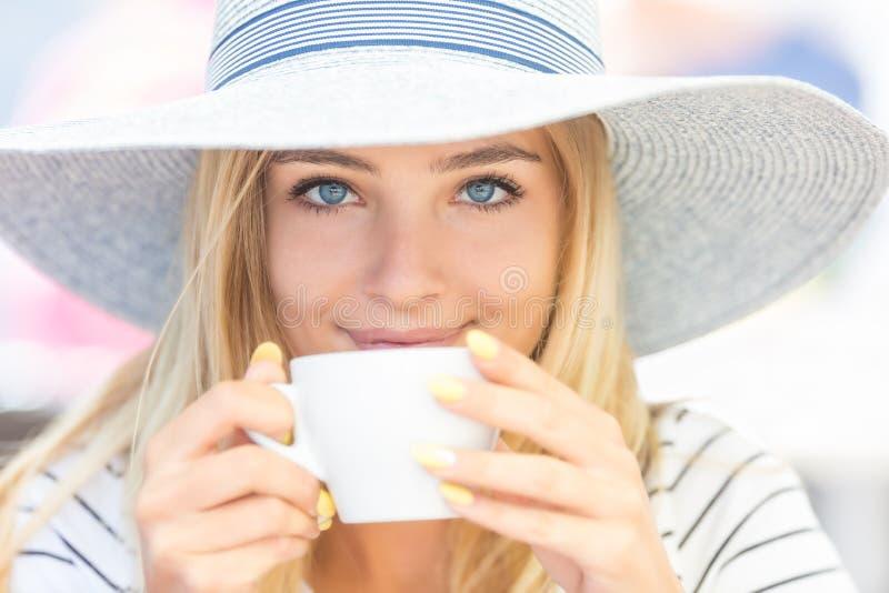 Café de consumición de la muchacha hermosa en una terraza del café Mujer joven del retrato del verano fotografía de archivo libre de regalías