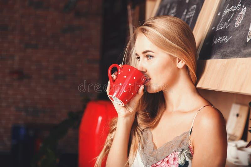 Café de consumición de la muchacha preciosa en la cocina imagen de archivo libre de regalías