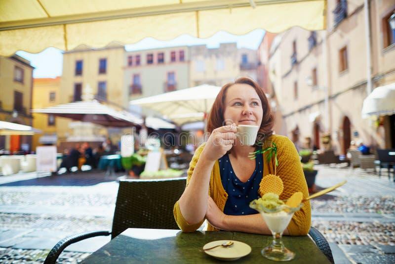 Café de consumición de la muchacha y consumición del helado en café italiano foto de archivo