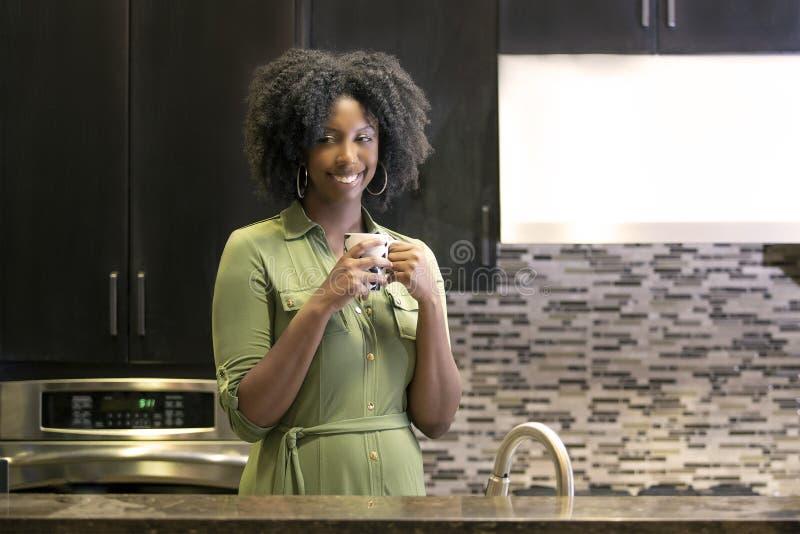 Caf? de consumici?n de la mujer afroamericana o t? de CBD en una cocina foto de archivo libre de regalías