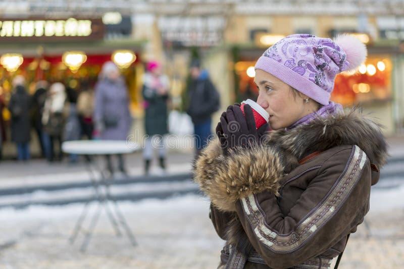 Café de consumición de la mujer hermosa en la calle de la ropa del invierno Retrato de la mujer sonriente elegante en la consumic foto de archivo