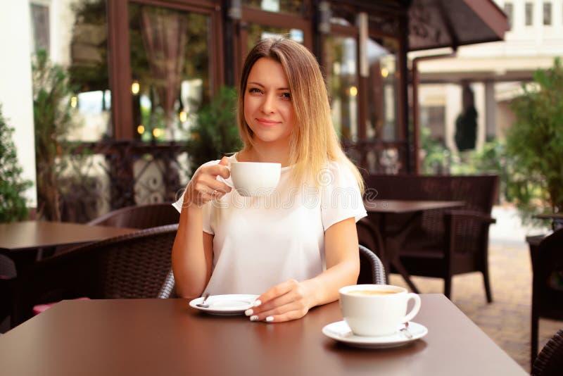 Café de consumición de la mujer hermosa en el café imagenes de archivo