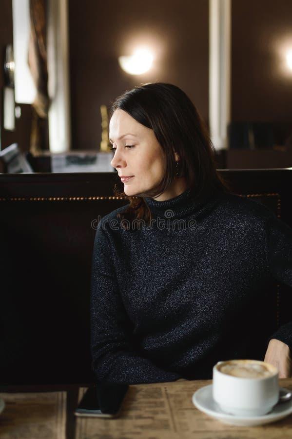 Café de consumición de la mujer hermosa en un café con un interior moderno hermoso Primer imagenes de archivo