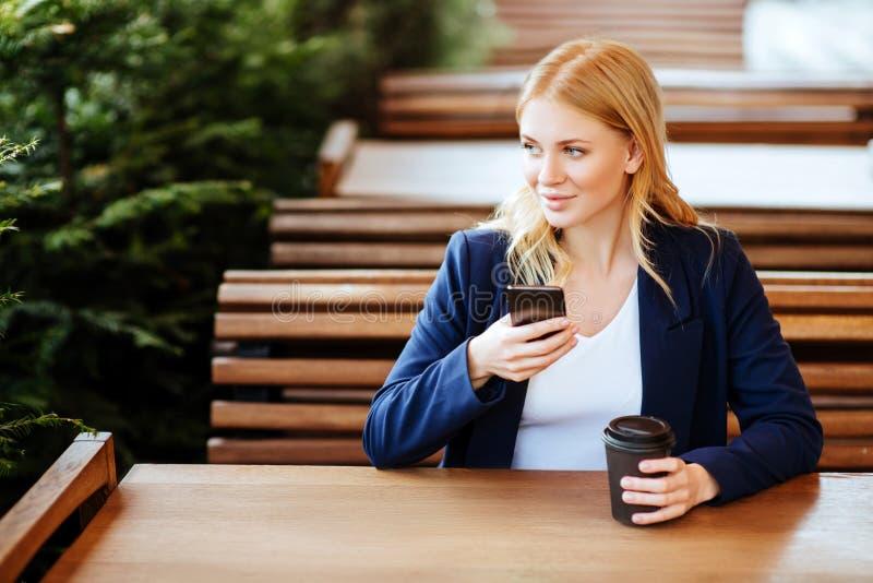 Café de consumición de la mujer hermosa en un café y un teléfono fotos de archivo libres de regalías