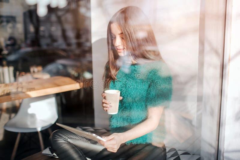 Café de consumición de la mujer hermosa joven en la barra del café Young modelo femenino que usa la tableta digital en el café imagen de archivo