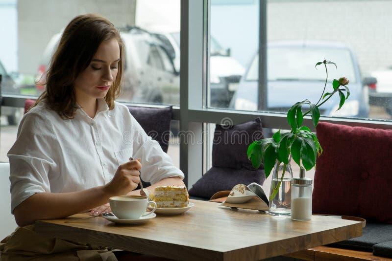 Café de consumición de la mujer hermosa joven en un café la mujer joven en negocio viste en una hora de la almuerzo foto de archivo libre de regalías