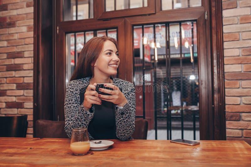 Café de consumición de la mujer joven en un café imagen de archivo