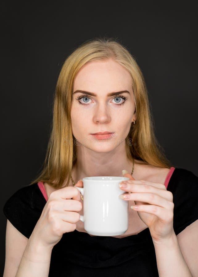 Café de consumición de la mujer joven Muchacha rubia con la taza de té blanca en un fondo gris fotografía de archivo